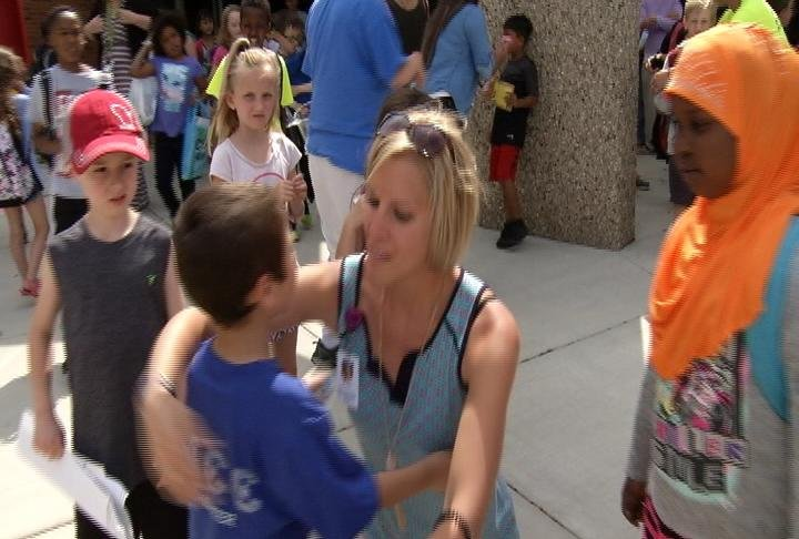 First grade STEM teacher at Gage Elementary Julie Ailts hugs a student goodbye and wishes him a fun summer.